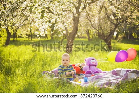 Little baby boy playing toys sitting on long green grass outside in backyard. Child holding green balloon in hand playing on spring day. Cute baby dressed in striped t-shirt of blue and green color. - stock photo