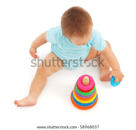Little baby boy playing with colorful ring toy - stock photo