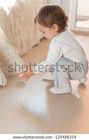 Little baby boy playing with silver Christmas balls on floor - stock photo