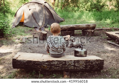 Little baby boy sitting at camping place on wood near campfire and tent. Tent, campfire on campsite outdoors. Travel, camping and adventure with child. Kid sitting at campsite. Little traveler. - stock photo