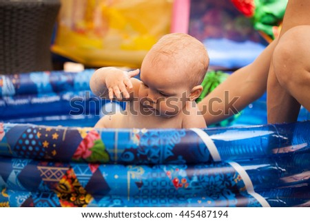 Little baby boy sitting in a blue rubber children's pool and playing with water - stock photo