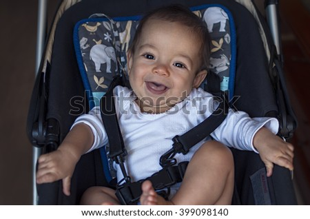 little baby boy sitting in a stroller in the home, ready for a walk in a pram - stock photo