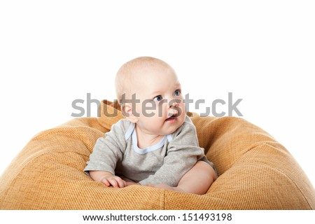 Little baby boy sitting in bean bag chair isolated over white - stock photo
