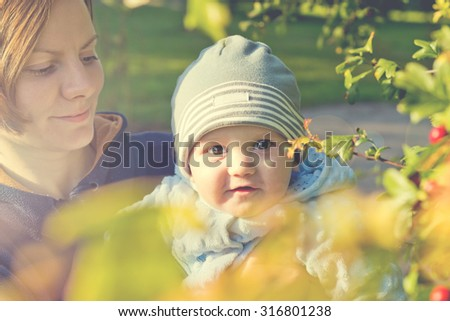 Little baby boy sitting on mother hands and smiling. Vintage portrait - stock photo