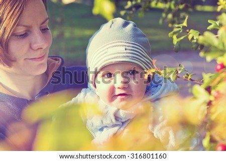 Little baby boy sitting on mother hands and smiling. Vintage style portrait - stock photo