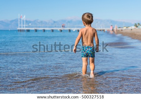 Little baby boy sitting playing in the sea. Positive human emotions, feelings, joy.