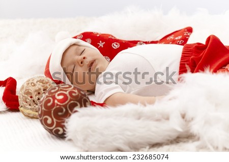 Little baby boy sleeping in santa hat with christmas decoration around him. - stock photo