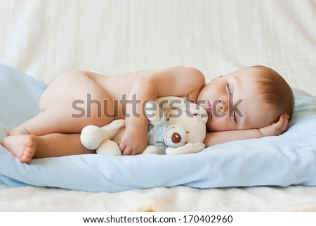 Little baby boy, sleeping with teddy bear - stock photo