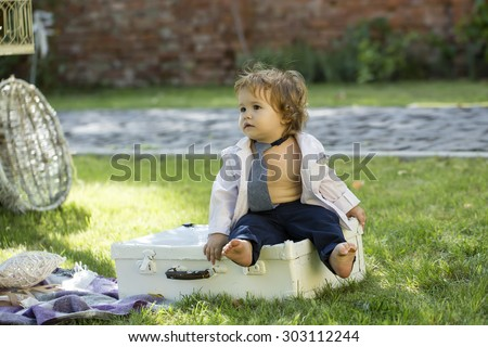 Little baby boy with blond hair in stylish tie unbuttoned shirt and trausers sitting on white vintage briefcase violet plaid on green grass sunny day outdoor, horizontal photo - stock photo