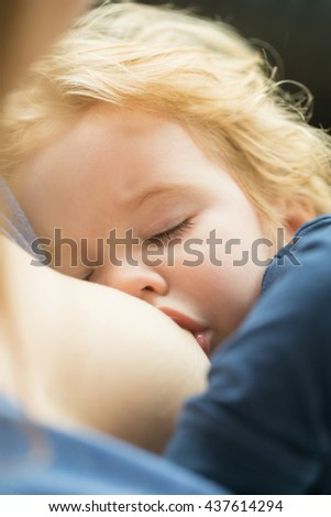 Little baby boy with blonde hair sucking female breast with closed eyes outdoor closeup - stock photo