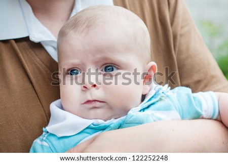 Little baby boy with blue eyes on father's arm in summer
