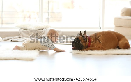 Little baby boy with boxer dog lying at home - stock photo