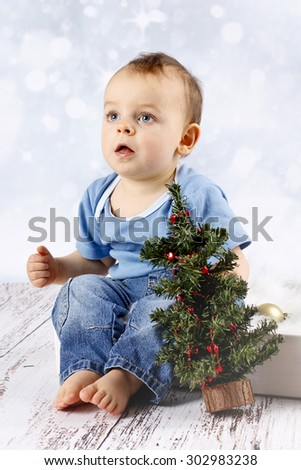 Little baby boy with christmas tree - stock photo