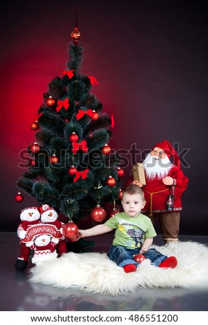little baby boy with christmas tree and santa on red background