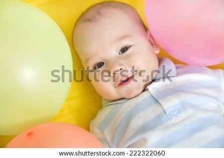 little baby boy with colorful balloons smiling at the camera - stock photo
