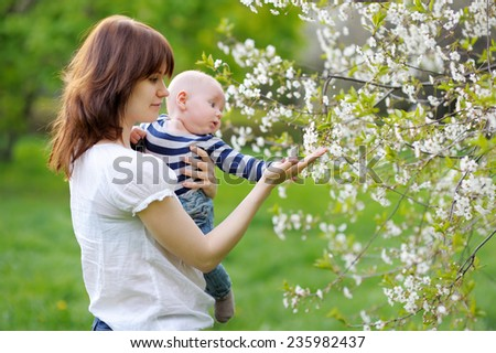 Little baby boy with her young mother in the blossom garden
