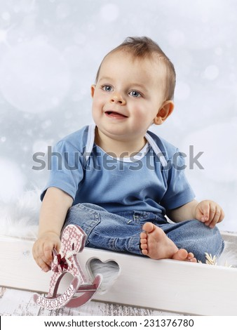 Little baby boy with rocking horse - stock photo