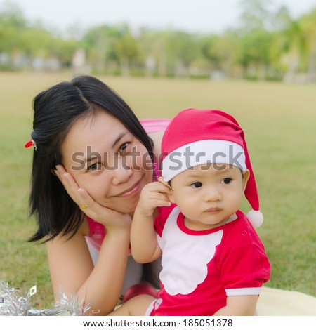 Little Baby Boy with Santa Claus suit in the Garden. - stock photo