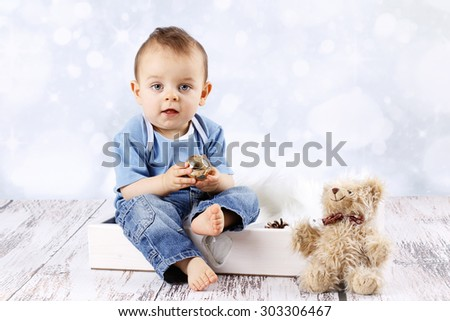 Little baby boy with teddy bear holding christmas ball