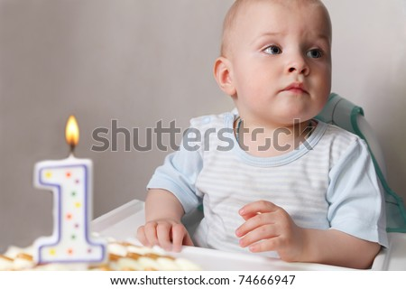 "Little baby celebrating its first birthday, in front of him cake with candle in the form of ""1"" - stock photo"