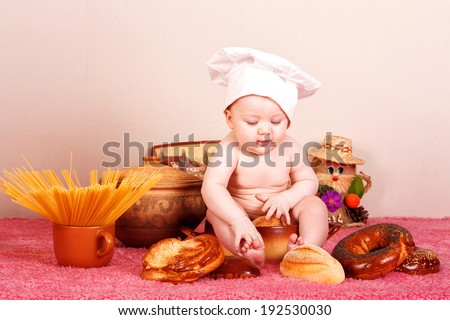 little baby chef .little baby in the cook costume at the kitchen with bread  - stock photo