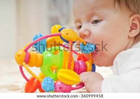 Little baby chewing a toy - stock photo