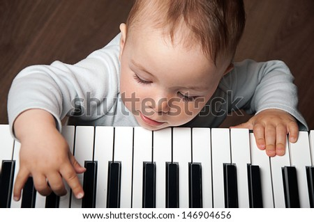 little baby child  play music on black and white piano keyboard