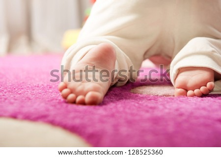 Little baby crawling on the pink carpet. Rear view - stock photo