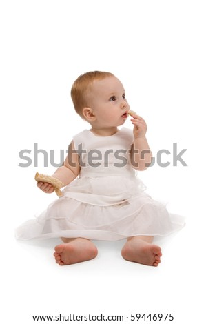 Little baby eating bread isolated on white - stock photo