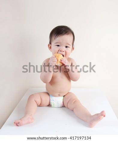 little baby eating bun - stock photo