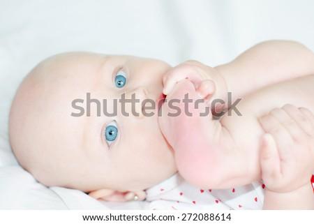 Little baby eating her feet - stock photo