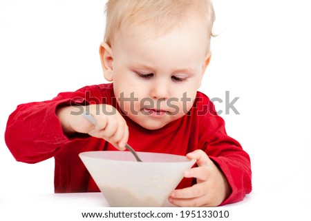 Little baby eating with spoon, isolated over white - stock photo