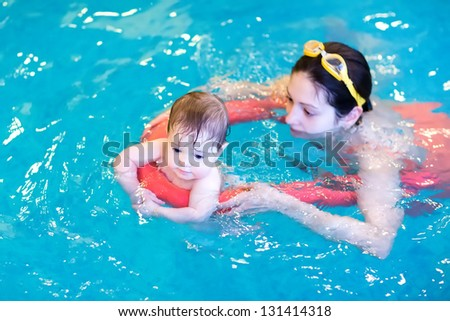 Little baby enjoying swimming pool with her mother - stock photo