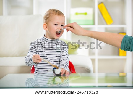Little baby feeding with a spoon - stock photo