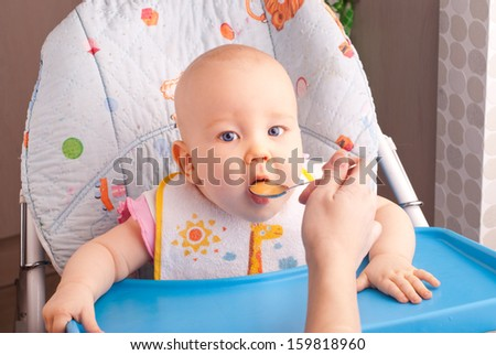 Little baby feeding with a spoon at the kitchen - stock photo