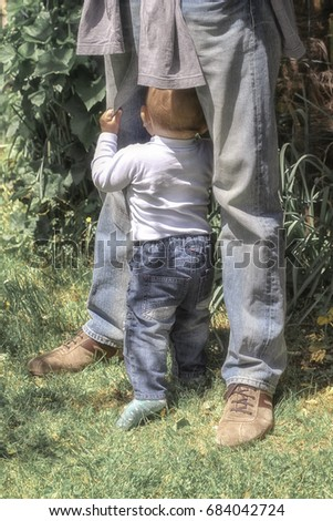Little baby feeling safe hiding behind the legs of his dad.