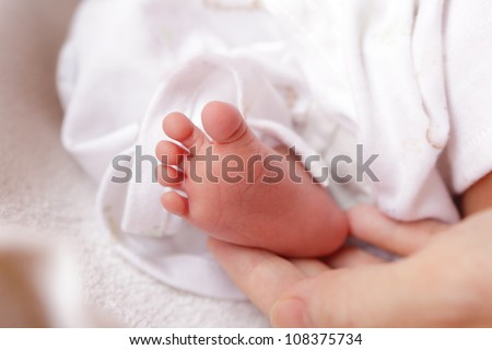Little baby feet with mother hand, baby is a asian