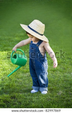 little baby gardener lost in the moment with the sun shinning in his face while he works hard - stock photo