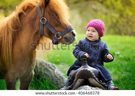 Little baby girl and pony - stock photo
