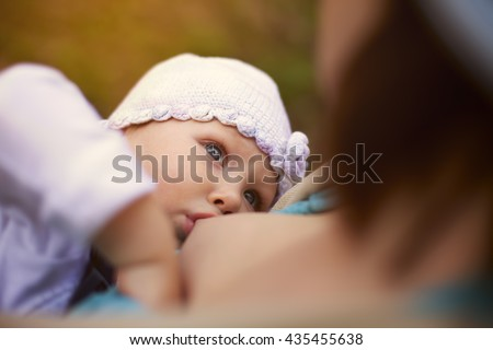 Little baby girl breast feeding outdoor - stock photo