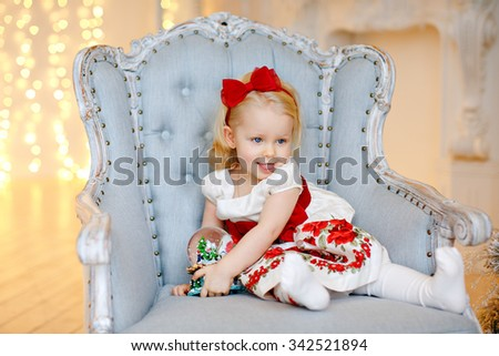 Little baby girl charming blonde in a red gown poses a face, sitting in a chair against a background of Christmas trees and holding ball in the interior of the house - stock photo