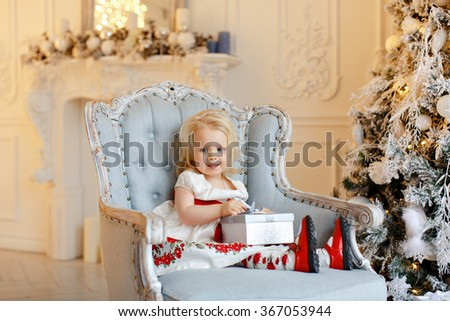 Little baby girl charming blonde, smiling and sitting in a chair against a background of Christmas trees and holding a gift, in the interior of the house - stock photo