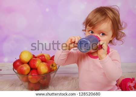little baby girl drinking an apple juice from bottle and sitting next to large glass bowl of fresh fruits - stock photo