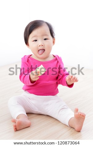 Little Baby Girl eat cookies and sticking her tongue out on living room at home, asian child - stock photo