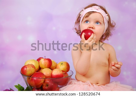little baby girl eating an apple and sitting next to large glass bowl of fresh fruits - stock photo
