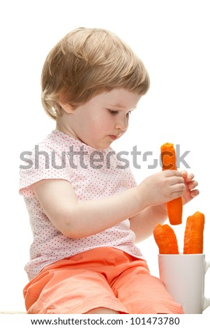 Little baby girl eating fresh carrot isolated on white