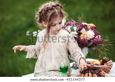 Little baby girl eats chocolate cake in nature at a picnic. The concept of a happy childhood