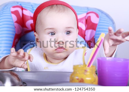 Little baby girl eats her first lunch - stock photo