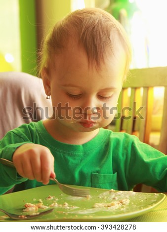 Little baby girl eats pancakes with cheese (children's food, bio, health) - stock photo