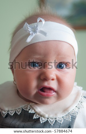 Little baby girl face looking at the camera - stock photo